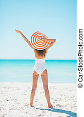 Young woman in hat rejoicing on beach. rear view