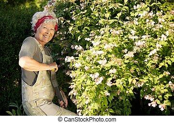 Elder woman gardening in backyard - Portrait of active...