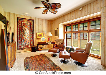 Furnished wood plank paneled room with rugs - Wood plank...