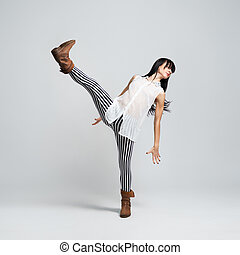 girl in boots takes a big step throwing high leg