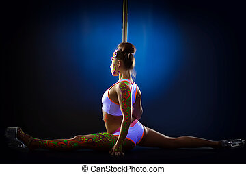 Flexible athletic dancer posing on splits, on blue...