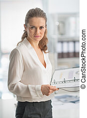 Portrait of modern business woman with documents in office
