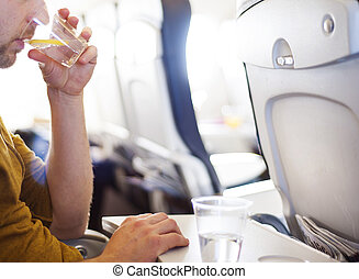Man in the aircraft is drinking water - Happy man seating in...