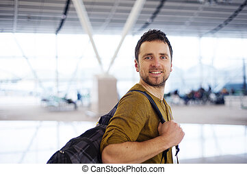 Happy man at the airport is going for holiday - Young man is...