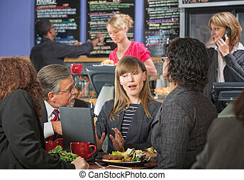 Business People Talking in Cafe - Serious adult business...