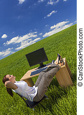 Woman Relaxing at Office Desk in Green Field - Business...