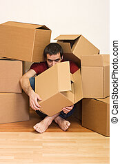 Man under cardboard boxes on the floor - moving concept