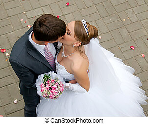 groom kisses the bride on the background of scattered rose...
