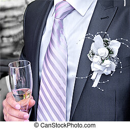 bridegroom is with a glass of champagne in hand
