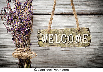 Welcome - On the wood background of a plaque with an...