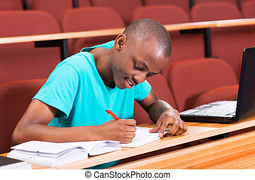 male african college student writting classwork - handsome...