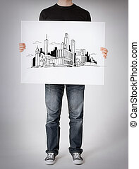man showing white board with city sketch