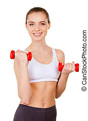 Exercising with dumbbells. Beautiful young woman in sports clothing training with dumbbells and smiling while standing isolated on white