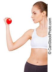 Weight training. Side view of beautiful young woman in...
