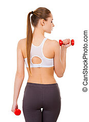Weight training. Rear view of beautiful young woman in...