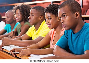 group of african american university students studying in...