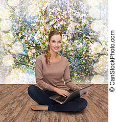 young woman sitting on floor with laptop