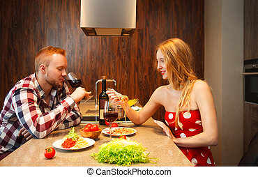 Happy woman eating pasts while man tasting red wine in a...