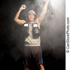 Serious young boxer raising his fists high into the air...