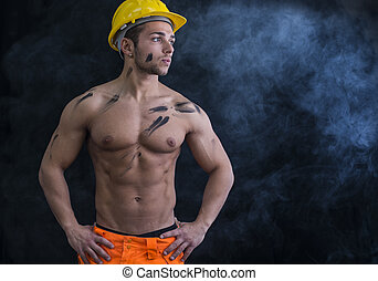 Muscular young construction worker shirtless wearing hardhat