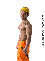 Profile view of muscular young construction worker shirtless