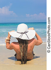 Back view of young woman sitting in hat on white sand beach enjoying summer holidays looking at the ocean.