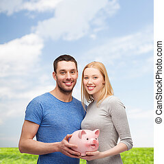 smiling couple holding big piggy bank - finance, money and...