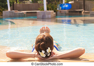 Young beautiful girl enjoying in luxury quiet swimmingpool