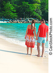 Back view of Young couple enjoying each other on a tropical beach