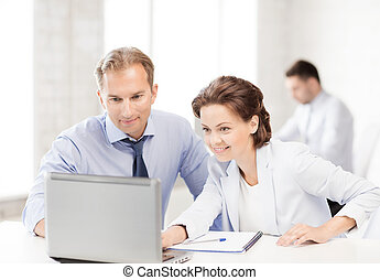man and woman working with laptop in office - smiling...