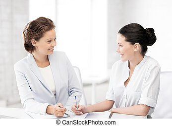 two businesswomen having discussion in office - picture of...