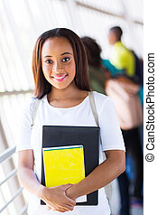 cute female african american college student holding books