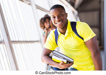 male afro american student holding books - cheerful male...