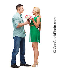 smiling couple with flower bouquet - happiness, holidays,...