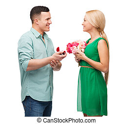 smiling couple with flower bouquet and ring - happiness,...