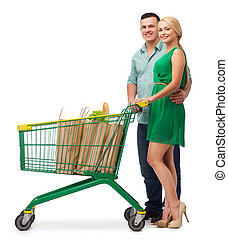 smiling couple with shopping cart and food in it -...