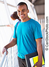 male african college student holding books - handsome male...