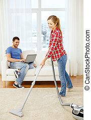 smiling woman with hoover and man with laptop - home,...