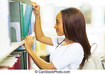 female african college student pulling a library book -...
