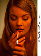 Young woman with lighter lighting up cigarette Girl smoking...