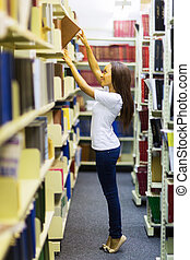 young african college student reaching for a book in library