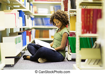 female african american student sitting on the floor reading...