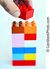 Building blocks - Mans hand puts a red toy block on top of a...