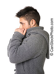 Profile of young man wearing sweater covering mouth with hands
