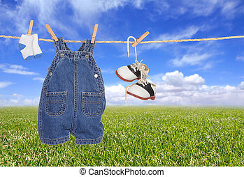 Baby Boy Child Clothes Hanging Outdoors Against a Bright...