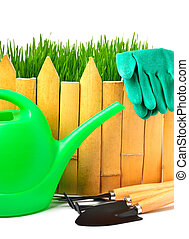 rake, shovel, rubber gloves, watering can against the wooden fence isolated on white