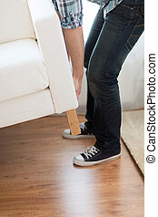 close up of male lifting up sofa to move - home, real estate...
