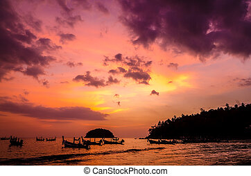 Seascape sunset with long-tail boat at Kata Beach, Thailand