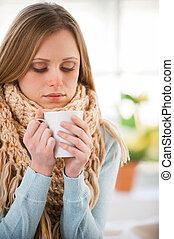 Drinking hot tea Young woman in scurf drinking hot tea while...