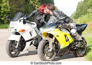 man and woman on motorcycles - young man and woman kissing...